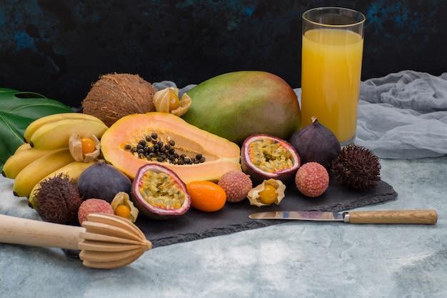 Exotische früchte, ein glas saft, eine manuelle saftpresse und ein messer