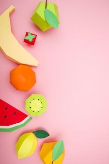 Exotische früchte gemacht vom papier auf rosa hintergrund