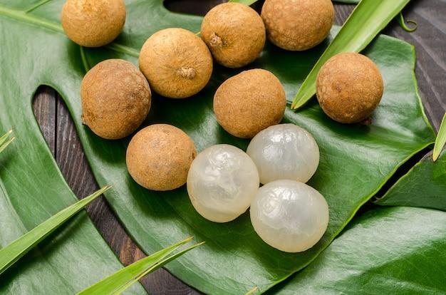 Exotische früchtelongan, lam-yay oder drachenauge. mehrere früchte auf monstera und palmblättern.
