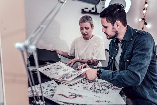 Exotische gutaussehende frau. professionelle tattoo-meisterin, die alle ihre skizzen und designs zeigt, während der kunde eine für ihn auswählt