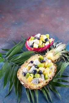 Exotischer obstsalat diente zur hälfte ananas auf palmblättern auf steinhintergrund. gesundes essen