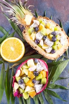 Exotischer obstsalat diente zur hälfte drachefrucht und -ananas mit palmblatt auf steinhintergrund, kopienraum. draufsicht