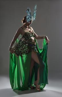 Exotischer tänzer im grünen kostüm mit federn