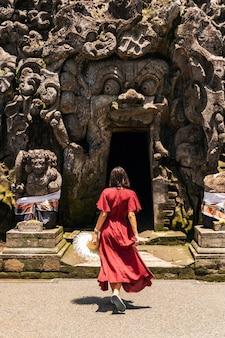 Exotischer tourismus. entspannte junge frau mit langem kleid beim gehen in der nähe des heiligen ortes auf bali place
