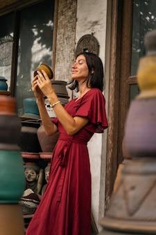 Exotisches land. erfreute brünette frau, die ein lächeln auf ihrem gesicht behält, während sie ihren ausflug auf dem lokalen markt genießt