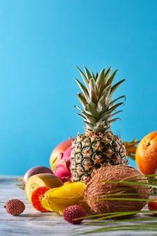Exotisches palmblatt der verschiedenen früchte auf einem grauen holztisch