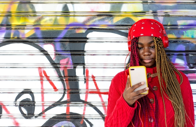 Exotisches schwarzes mädchen mit farbigen zöpfen unter verwendung ihres handys. gekleidet in einen roten pullover und ein rotes kopftuch. an eine graffiti-wand gelehnt.