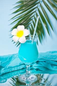 Exotisches tropisches blue curacao cocktailgetränk in einem glas mit plumeria frangipani blume, palmblatt, frischer kokosnuss