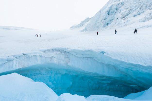 Expedition von wanderern in den schneebedeckten steilen bergen
