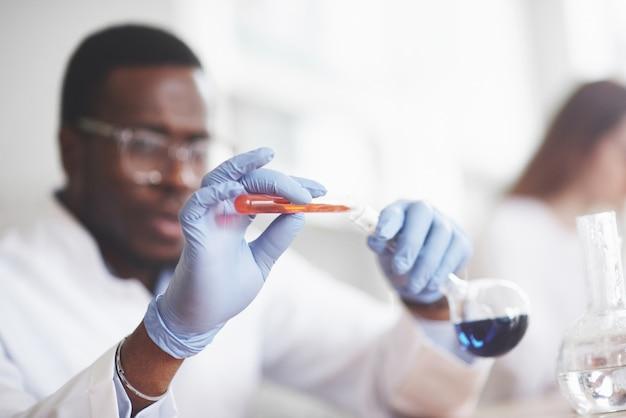 Experimente im chemischen labor. ein experiment wurde in einem labor in transparenten kolben durchgeführt.