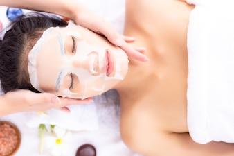 Experte der Massage massiert schönes Frauengesicht und benutzt die Kollagenmaske, die auf ihr Gesicht gesetzt wird