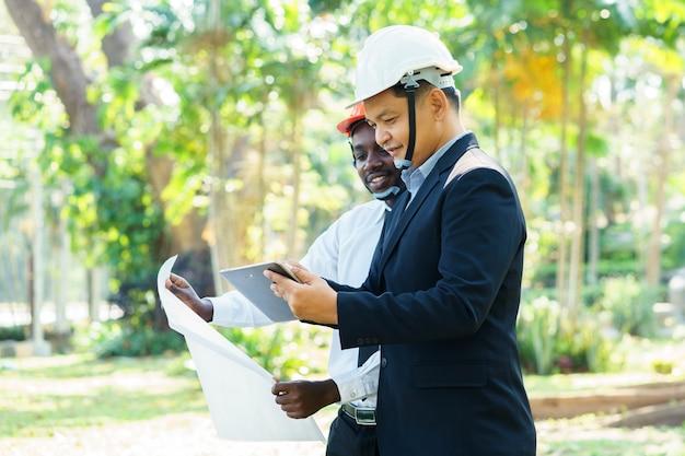 Experte-teamplan des asiatischen und afrikanischen architekteningenieurs zwei mit lächeln in der grünen natur.
