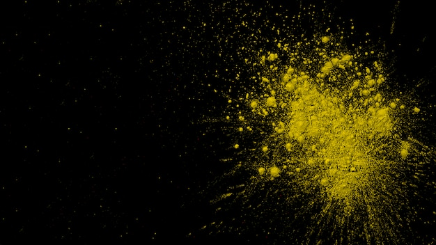 Explosion der trockenen gelben farbe auf schwarzem hintergrund