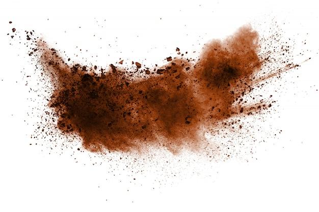 Explosion des dunkelbraunen pulvers auf weißem hintergrund.