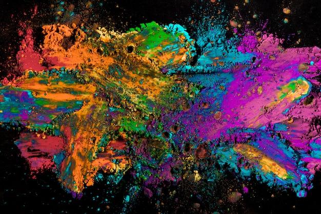 Explosion des farbigen pulvers auf schwarzer oberfläche