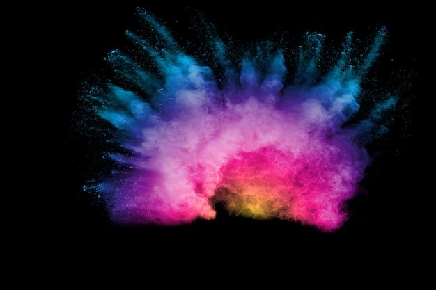 Explosion des farbpulvers auf schwarzem hintergrund. spritzen des farbpulverstaubes auf dunklem hintergrund