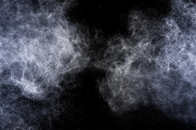 Explosion von blauem pulver auf schwarzem hintergrund
