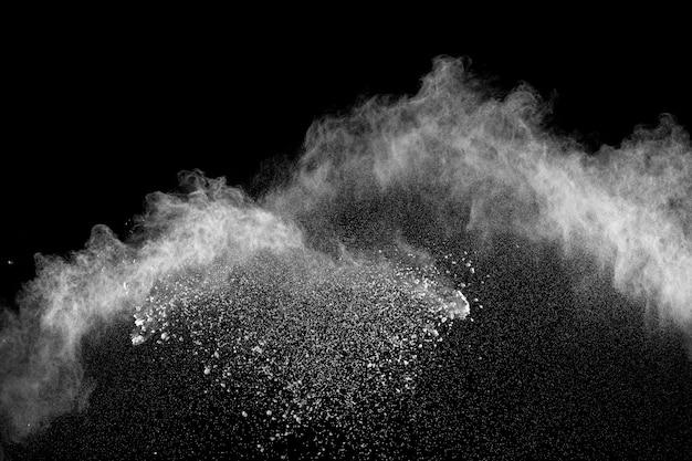 Explosionwolke des weißen pulvers gegen schwarzen hintergrund. weißes staubteilchenspritzen.