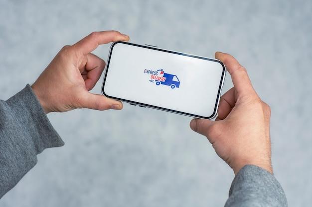 Express-lieferung in ihrem telefon. ein mann hält ein smartphone mit einem symbol auf einem weißen bildschirm in den händen.