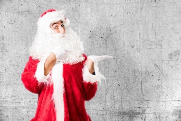 Expressive weihnachtsmann auf seiner linken hand zeigt