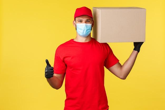 Expresslieferung während der pandemie, covid-19, sicherer versand, online-shopping-konzept. starker junger kurier in roter firmenuniform, box auf schulter und daumen hoch halten, paketsicherheit garantieren