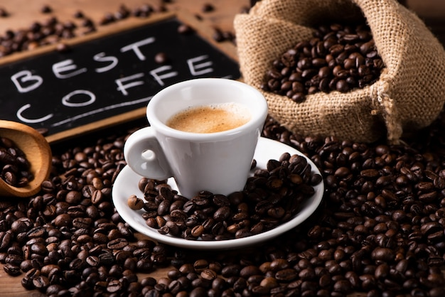 Expresso-kaffeetasse nahaufnahme über dunklen gerösteten kaffeebohnen