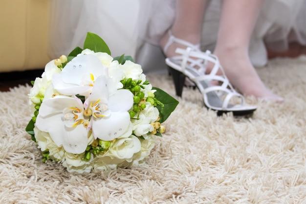Exquisiter hochzeitsstrauß aus weißen blumen: freesien, phalaenopsis-orchideen und rosen. brautschuhe im hintergrund