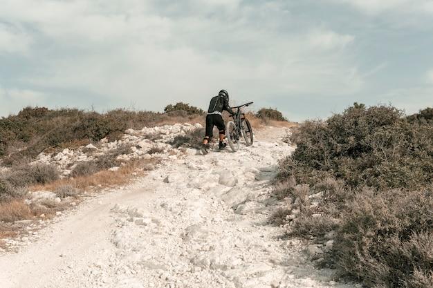 Extra langer schuss mann, der ein mountainbike reitet