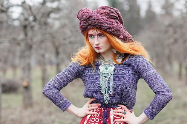 Extravagante rothaarige junge frau, die ethnischen schmuck, kleidung und turban mit ungewöhnlichem make-up tanzt oder in einem nebligen wald oder park posiert. psychedelische trance-musik, voodoo, esoterikakonzept