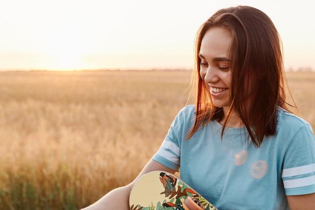 Extrem glückliche frau mit dunklen haaren, die blaues t-shirt trägt, das skateboard in den händen hält, wegschaut, positive emotionen ausdrückt, mit feld und sonnenuntergang im hintergrund posiert.