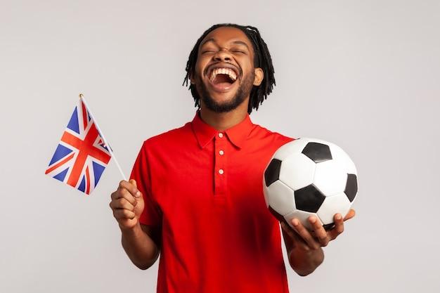 Extrem glücklicher mann mit britischer flagge, der für sein lieblingsteam jubelt und sich freut, zu gewinnen.