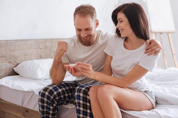 Extrem glückliches paar, das auf einem bett sitzt und sich umarmt, während es die ergebnisse eines schwangerschaftstests herausfindet