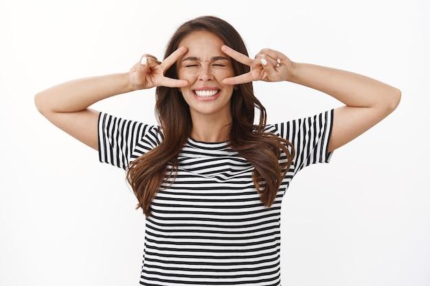Extrem glückliches, sorgloses junges verträumtes mädchen in gestreiftem t-shirt, enge augen, schielen und lächeln aufgeregt, zeigen friedens- oder siegeszeichen um das gesicht, jubeln und haben eine verspielte fröhliche stimmung