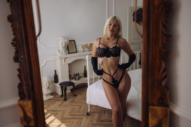 Extrem schöne und junge erwachsene kaukasische frau, die dessous in einem boudoir-schlafzimmer in verschiedenen posen trägt.