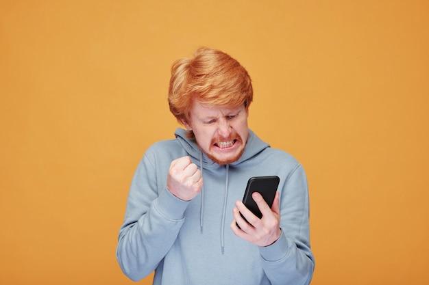 Extrem verärgerter junger bärtiger mann in der freizeitkleidung, der bildschirm des smartphones betrachtet, während er mit jemandem im video-chat argumentiert