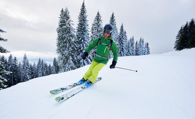 Extremer freeride-skifahrer des männlichen skifahrers backpacker auf der bewaldeten skipistenwüste