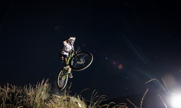 Extremer sprung auf einem mountainbike auf dem hügel gegen nächtlichen himmel