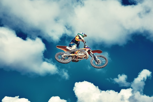 Extremes konzept, fordern sie sich extremen sprung auf einem motorrad über blauen himmel mit wolken heraus