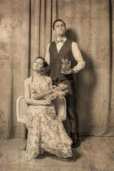 Exzentrisches eheportrait. die frau sitzt in einem eleganten blumenkleid und trägt eine spielzeugwaffe. der mann, stehend, trägt einen eleganten anzug und trägt ein spielzeugkätzchen. ernster und feierlicher ausdruck.
