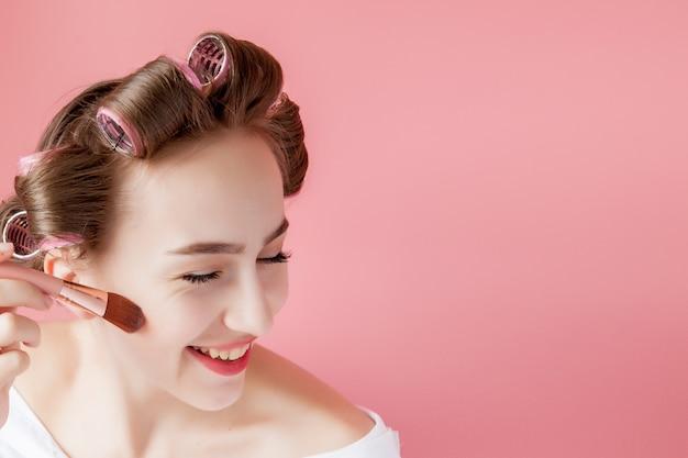 Eyeliner augen make-up schönheitspflege frau. mädchen, das augenstiftfarbe auf augen setzt, die in einem taschenspiegel schauen, der glücklich auf rosa hintergrund lächelt.