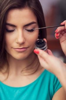 Eyeliner aus dem tintenfass mit einem make-up-pinsel auftragen