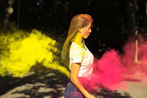 Fabelhafte blonde frau mit leuchtenden farben, die um sie herum explodieren, posiert beim holi-festival