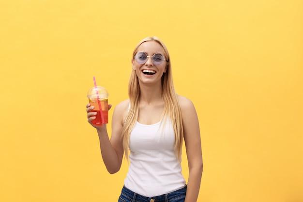 Fabelhafte frau in der sonnenbrille, die weißes t-shirt beim halten des glases safts lokalisiert über gelbem hintergrund trägt