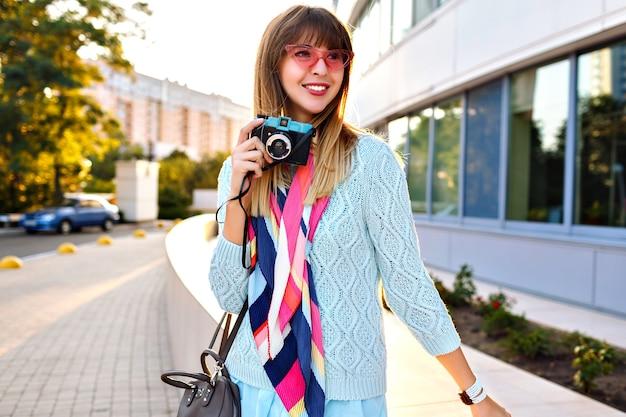 Fabelhafte junge stilvolle frau, die auf der straße, romantisches elegantes outfit, pulloverschal und sonnenbrille aufwirft, vintage-kameraende hält, die zeit genießt.