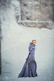 Fabelhafte mädchen elfe geht in der nähe einer alten festung und schneebedeckten winter natur