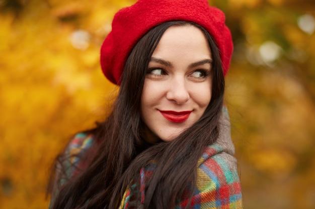 Fabelhafte romantische frau mit langen dunklen haaren, die rote baskenmütze auf unscharfem herbstwald tragen. mädchen im wald mit orange herbstlaub