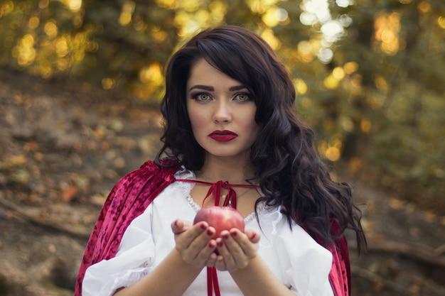 Fabelhaftes porträt einer frau mit einem roten apfel, schneeweißes cosplay