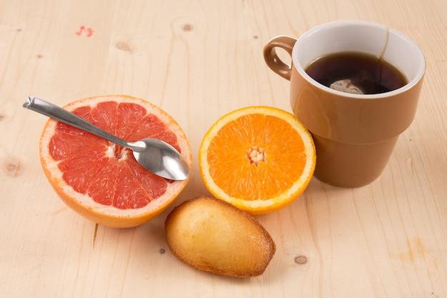 Fabelhaftes und sehr süßes frühstück bestehend aus tee, frischem obst, kuchen