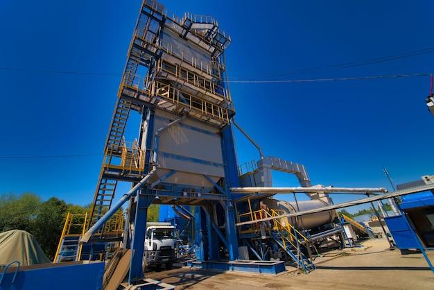 Fabrik für asphaltproduktion auf blauem himmelhintergrund