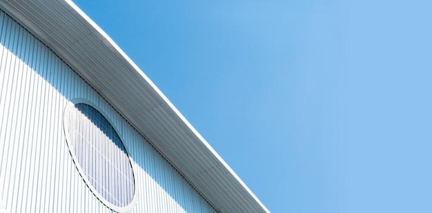 Fabrik-lagerdach mit bewölktem blauem himmel